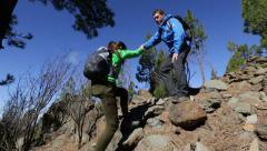 Helping hand - hiking woman getting help on hike Stock Footage