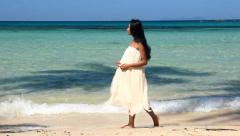 Pregnant woman walking on the beach Stock Footage