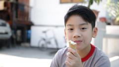 Asian kid enjoy delicious ice cream cone during the summer. Stock Footage