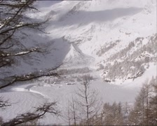 Vehicle shot - high angle view from train at snow covered valley with settlement Stock Footage