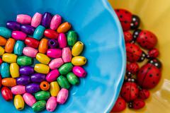 Multi colored beads in colourful dishes, top view, selective focus Stock Photos