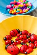 Multi colored beads in colourful dishes on white wooden table Stock Photos