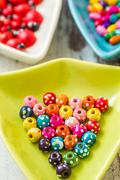 multi colored beads in colourful dishes on white wooden table - stock photo