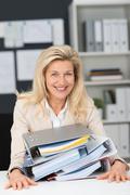 Hardworking businesswoman with office binders Stock Photos
