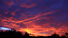 4K Vibrant Red Puffy Clouds Silhouetted Landscape Time Lapse Stock Footage
