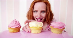 Young red head woman is eating cupcakes in slow motion Stock Footage