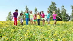 Large group of children run in dandelion field - stock footage