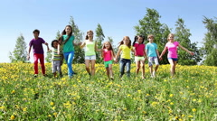 Large group of kids run in dandelion field Stock Footage