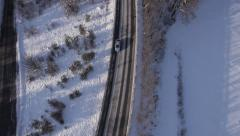 Aerial - Single car driving along a road in winter, slow motion - stock footage