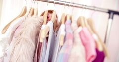 Young Woman Looking Through Clothing on hangers Stock Footage