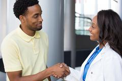 Closeup portrait of healthcare professional shaking hands with patient in yel Stock Photos