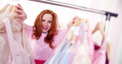 Young Woman Looking Through Clothing on hangers - stock footage