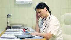 Female doctor having headache while working on tablet in hospital HD Stock Footage