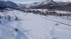 Aerial - Rural mountain region landscape covered in snow. Cars driving on a road Stock Footage