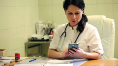 Stock Video Footage of Young female doctor sitting with smartphone in the hospital HD