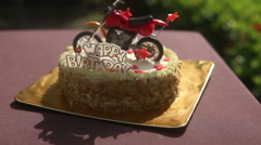 Birthday cake decorated with motorcycle and red stars Stock Footage