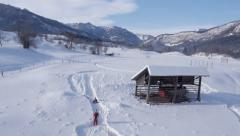 Aerial - Child running across snow covered field, slow motion Stock Footage