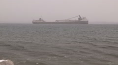 Ship / frieghter taking shelter in bay from severe wind waves and blizzard Stock Footage
