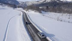 Aerial - Cars driving on a two-lane road through a snowy landscape Stock Footage