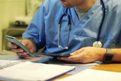Young male doctor sitting with smartphone in the hospital NTSC Stock Footage