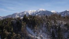 Aerial - Snow-capped mountain behind a hill Stock Footage