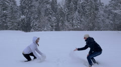 Young couple having a snowball fight in a snow field Arkistovideo