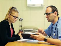 Doctor using tablet and talking about examination results in hospital NTSC - stock footage