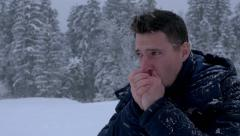 Young men rubbing his hands and coughing in a cold winter weather while snowing Stock Footage