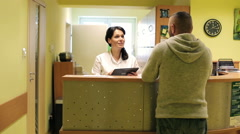 Patient and nurse with tablet conversing at hospital reception desk HD - stock footage