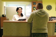 Patient and nurse with tablet conversing at hospital reception desk NTSC Stock Footage