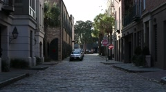 Cars driving down historic shaded cobblestone road Stock Footage