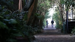 Romantic couple walking down narrow garden pathway Stock Footage