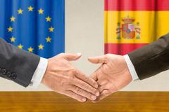 representatives of the eu and spain shake hands - stock photo