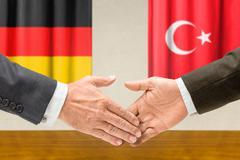 Representatives of germany and turkey shake hands Stock Photos