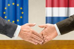 representatives of the eu and the netherlands shake hands - stock photo