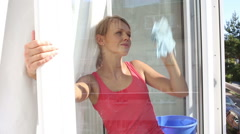Pretty, young woman doing house works, washing windows in her appartment Stock Footage