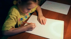 Cute little girl drawing with concentration on a piece of paper with a pe Stock Footage