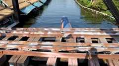 Longtail boat pass under the railway bridge at taling chan floating market Stock Footage