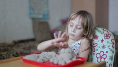 Little girl sculpts figures out of the sand Stock Footage