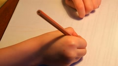Kid arms draw with a pencil on the sheet of paper Stock Footage