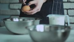 The woman breaks egg in a cup Stock Footage