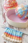 colorful knitting with spokes and ball of yarn on white wooden table - stock photo