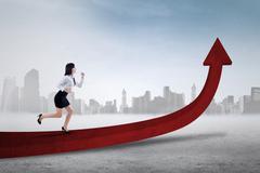 Businesswoman runs on the upward arrow Stock Photos