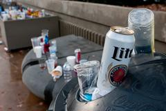 Beer cans and trash litter area outside sports stadium Stock Photos