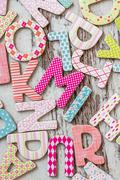 Random colorful uppercase letters with beautiful patterns on white wooden bac Stock Photos