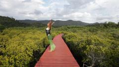 Sun Salutation Sequence (Surya Namaskar B) on board bridge above the forest Stock Footage