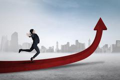 Female entrepreneur jumping on red arrow Stock Photos