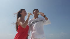 Charming Asian Man And His Beautiful Fiancee Enjoy Champagne At Seaside - stock footage
