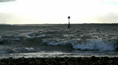 Lee-on-the-Solent waves breaking on stoney beach and groyne in sea Stock Footage
