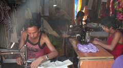 INDIA, GOA - 2012: The Indian men sew clothes for sale Stock Footage